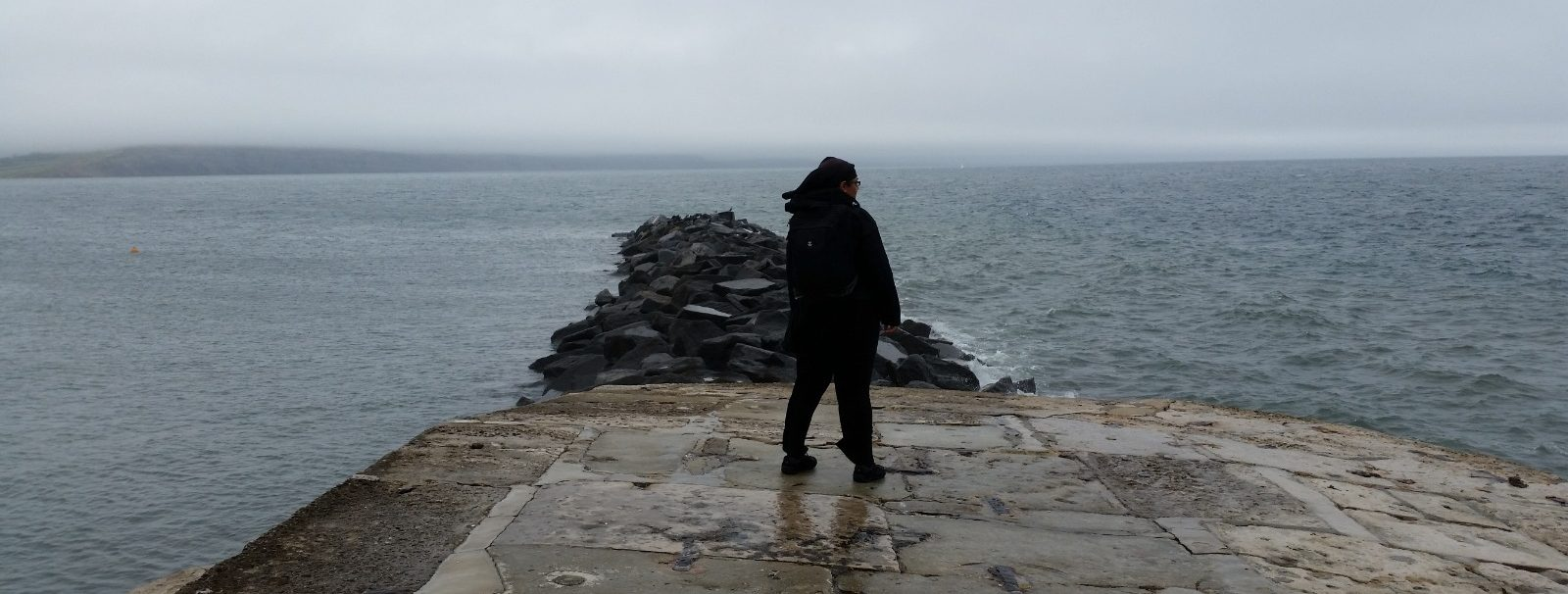 Author stood looking out to sea on the Cobb at Lyme Regis.